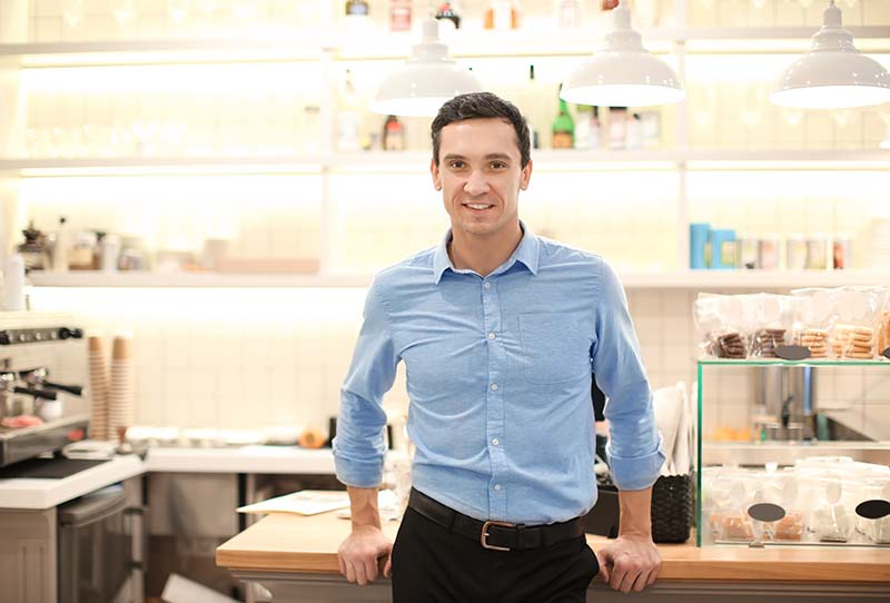 Young man standing in store. Small business owner portrait.